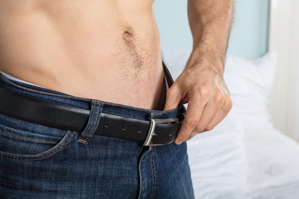 mand traekker lidt ned i baeltet som holder bukserne oppe 1024x682