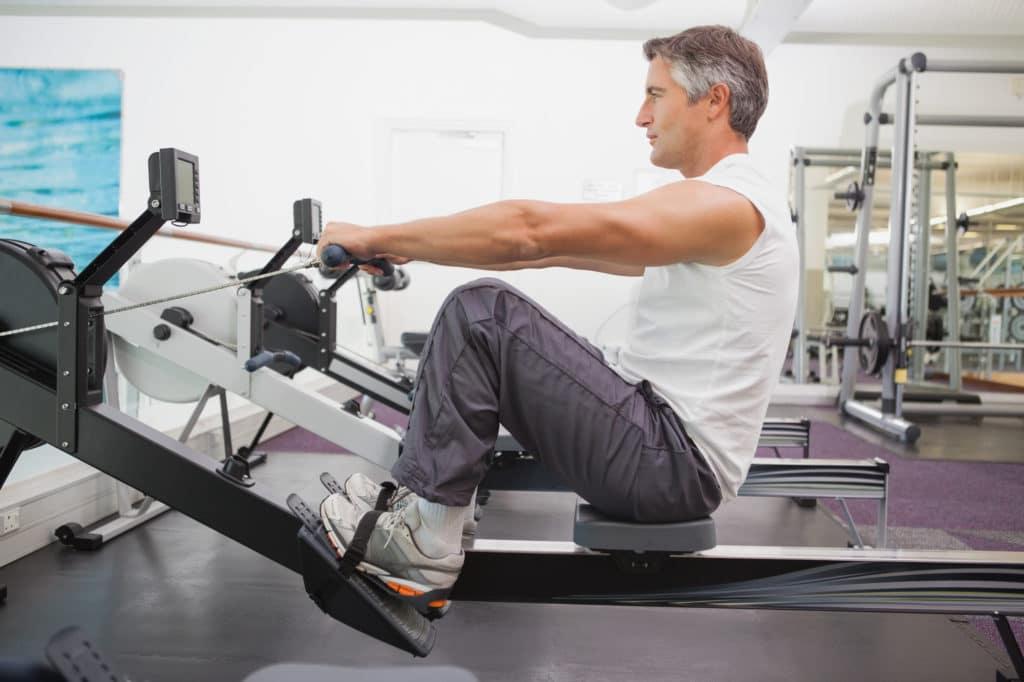 Midaldrende mand træner konditionstræning i en romaskine