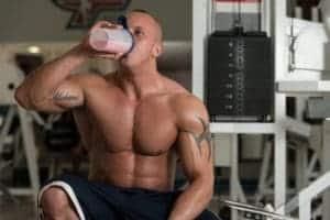 muskuloes mand med en proteinshake proteinpulver og weight gainer shake 300x200