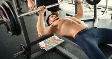 baenkpres mandlig bodybuilder traener baenkpres med vaegtstang 390x205