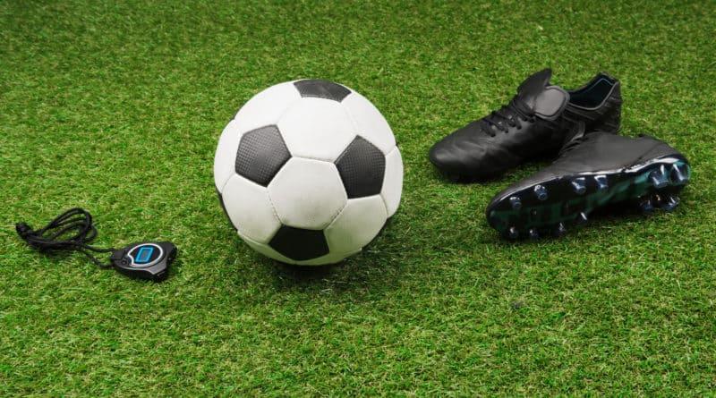 fodbold og fodboldstoevler paa groent graes 800x445