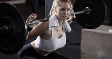 kvinde med haandklaede om nakken viser et squat 390x205
