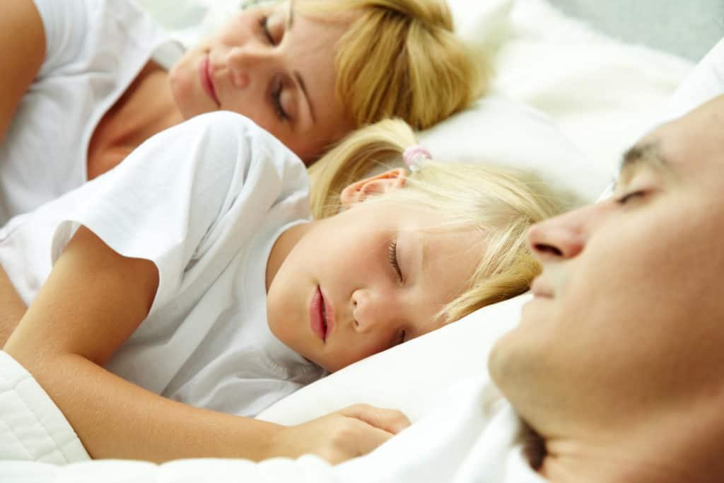lille pige sover mellem sine foraeldre familie 1024x683