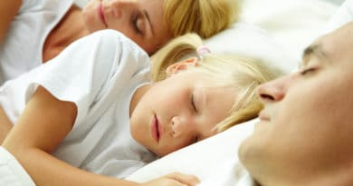 lille pige sover mellem sine foraeldre familie 390x205