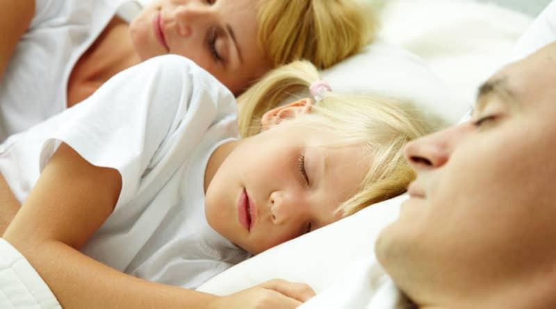 lille pige sover mellem sine foraeldre familie 800x445