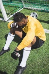 maalmand i en fodboldkamp sidder og aergrer sig over at der er gaaet et maal ind 200x300