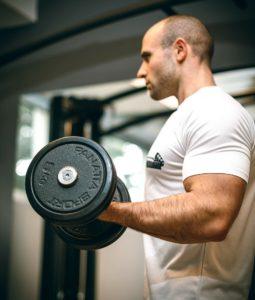 mand i hvid t shirt laver dumbbell curls med haandvaegte 255x300