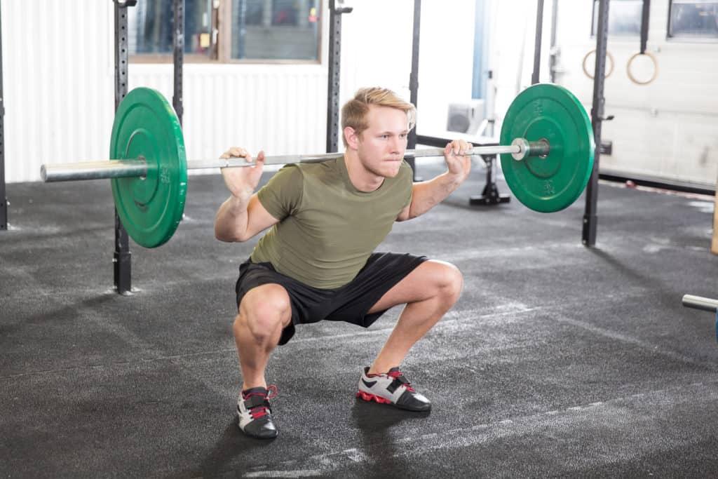squat mand med vaegtstang paa ryggen viser et korrekt squat 1024x683